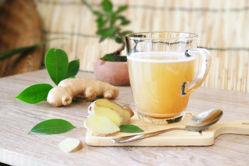 zenzero fette foglie tazza divetro con tisana cucchiaino tagliere legno