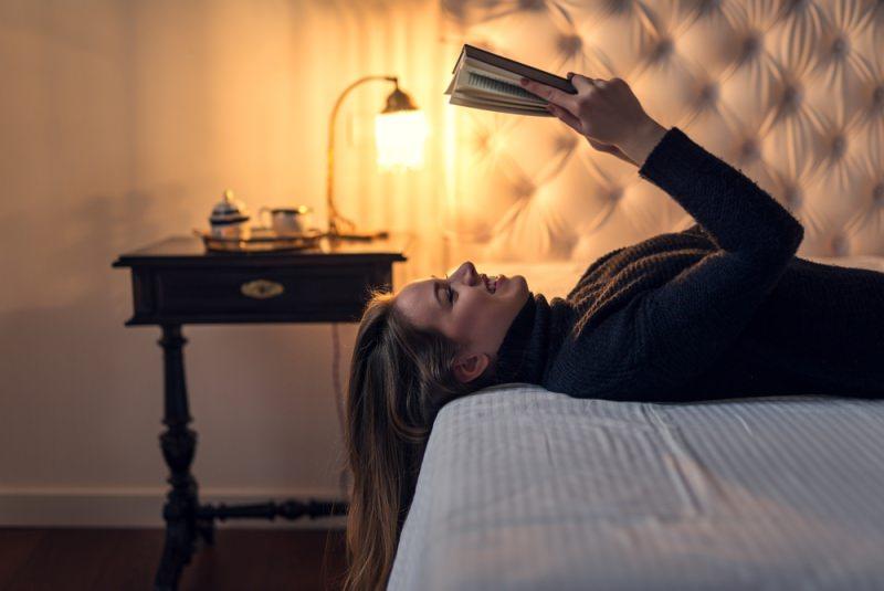 donna sorridente legge sul letto con luce calda comodino