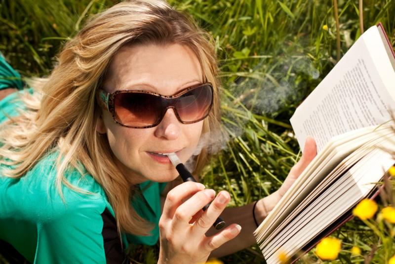 donna sigaretta elettronica svapa leggere libro occhiali da sole