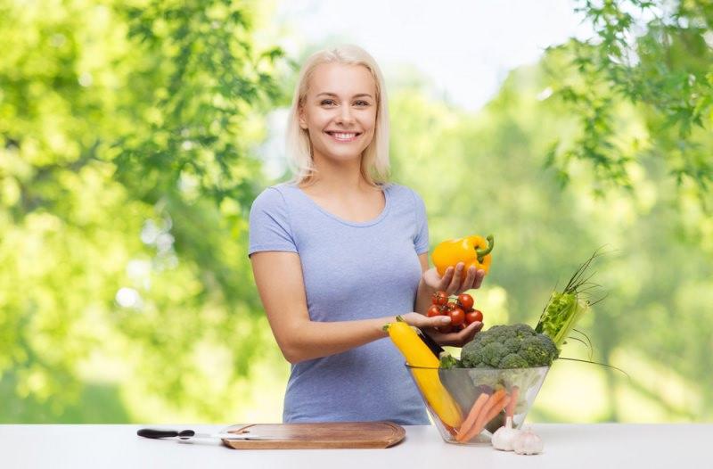 donna sorriso capelli biondi tagliere legno coltello ciotola vetro verdure peperone e pomodori mani