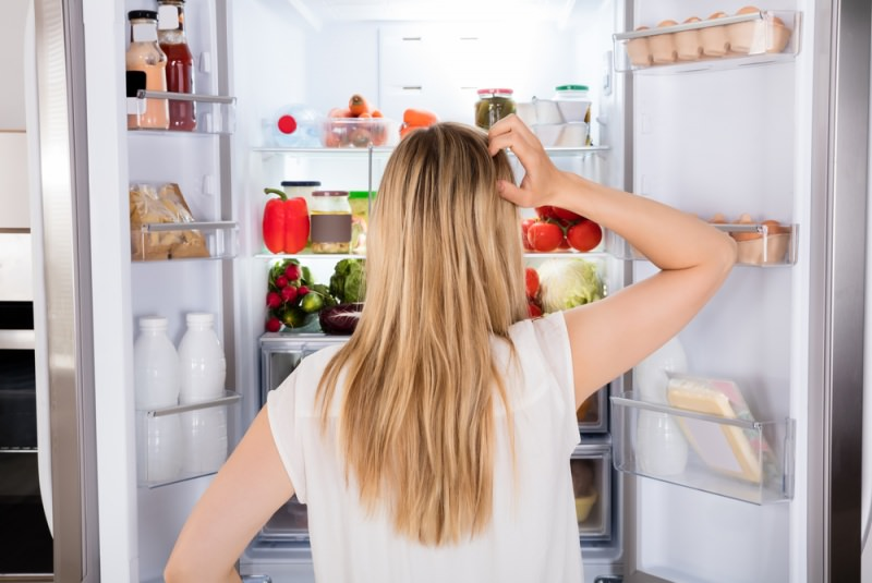 donna capelli biondi di spalle guarda interno frigorifero cibo