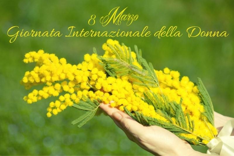 ramoscello di mimosa in mano donna 8 marzo giornata internazionale della donna