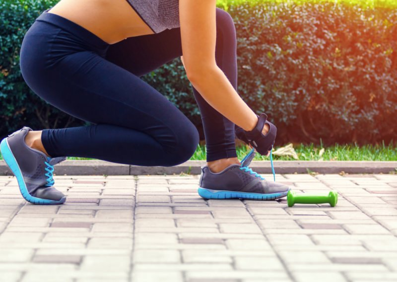 donna indossa leggins fitness all aperto allaccia sneackers manubrio peso
