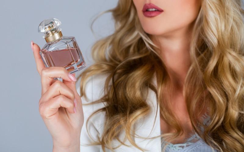 profumo in mano a bella donna capelli lunghi biondi