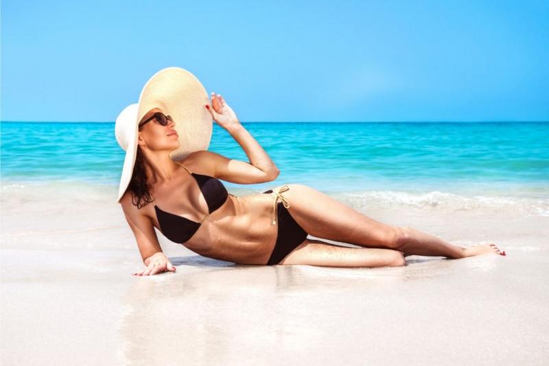 giovane bella ragazza distesa sulla sabbia mare estate bikini nero cappello paglia