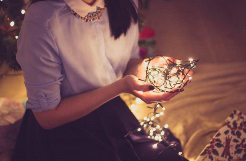 Natale 2017: i look per essere trendy ed eleganti donna camicia lilla colletto bianco collana capelli lisci neri luci led albero di natale mani unghie smalto gonna viola moda fshion