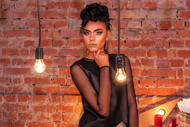 Natale 2017: i look per essere trendy ed eleganti viso donna maglia maniche a rete nera rossetto verde glitter lampadine muro