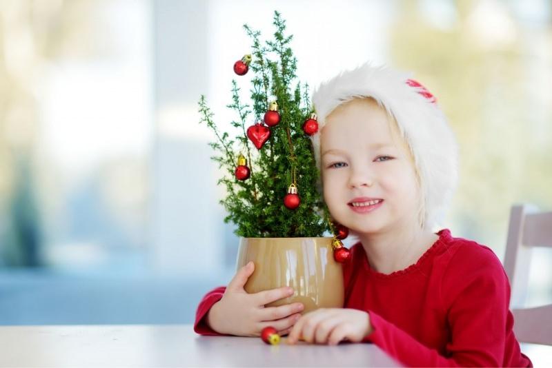 adorabile bellissima bambina vestita di rosso sorride e abbraccia piccolo albero di Natale decorato