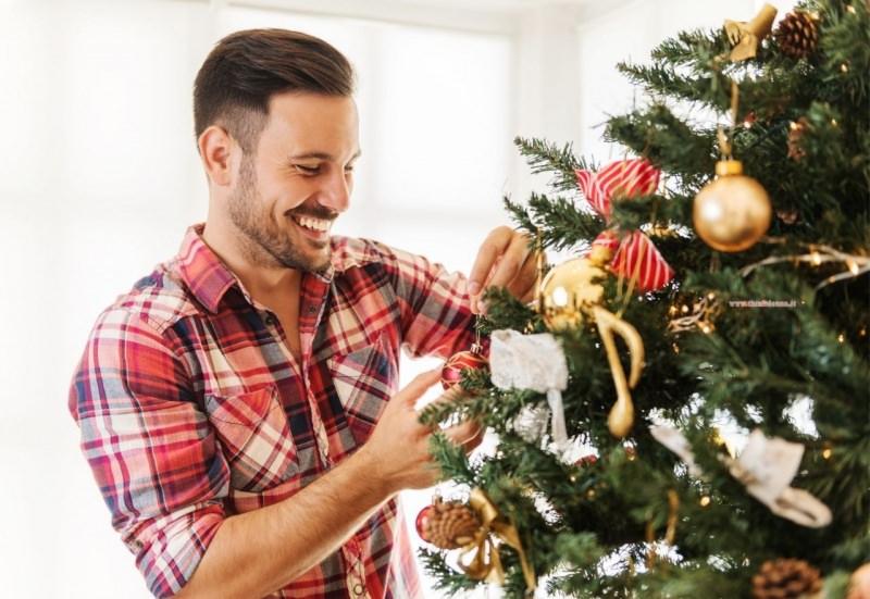 uomo decora albero di natale decorazioni vintage sorriso