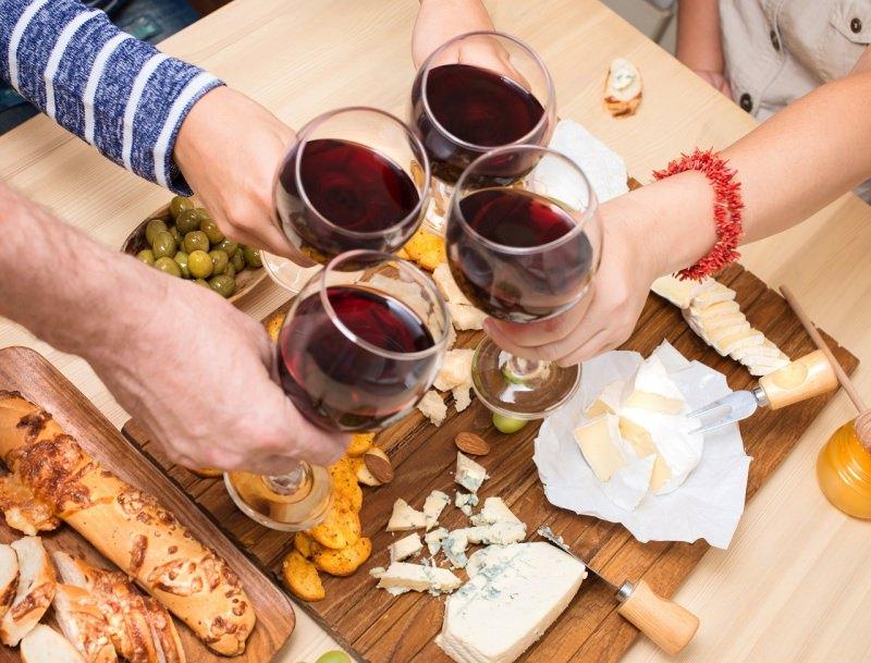 amici antipasto brindisi calici vino rosso tagliere formaggi pane