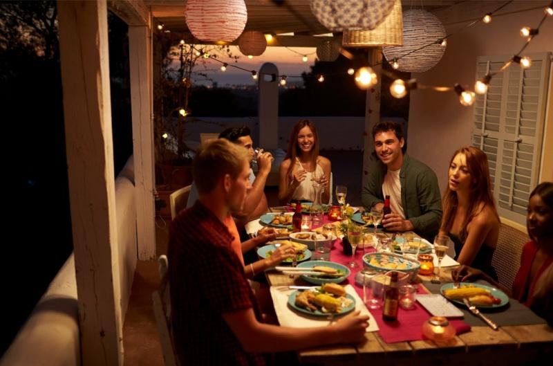 cena all'aperto amici tavola apparecchiata stringhe luci