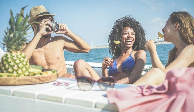 uomo con macchina fotografica barca mare ragazze mangiano frutta sulla barca estate abbornzatura