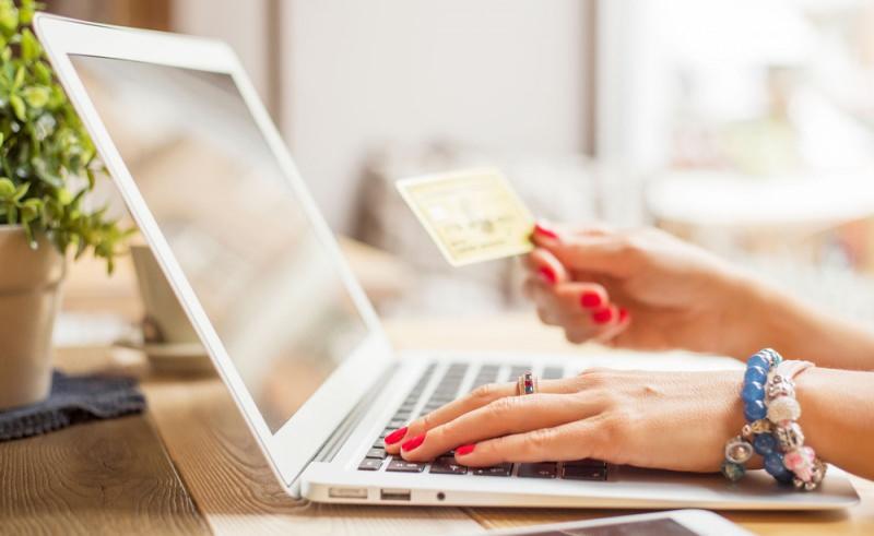 Acquistare gli anelli su internet risparmiando: ecco come comprare online carta di credito laptop notebook mano donna smalto rosso anello bracciali perle colorate azzurro tavolo legno piantina verde