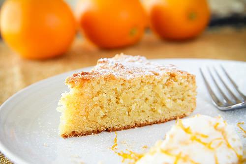 Torta all'arancia e mandorle Dolce dell'Immacolata ricetta ingredienti fetta arance piatto bianco zucchero a velo succo forchetta tavola cucina