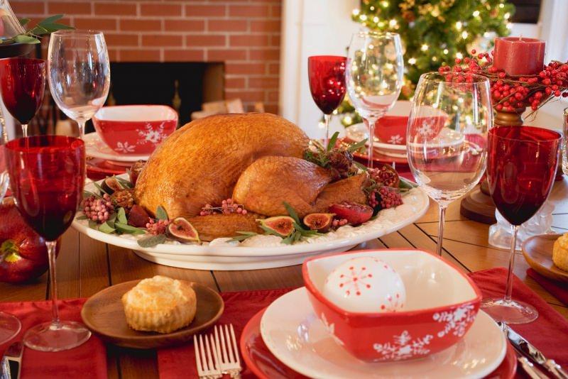 tavola apparecchiata in rosso a festa arrosto di tacchino calici luci albero di natale