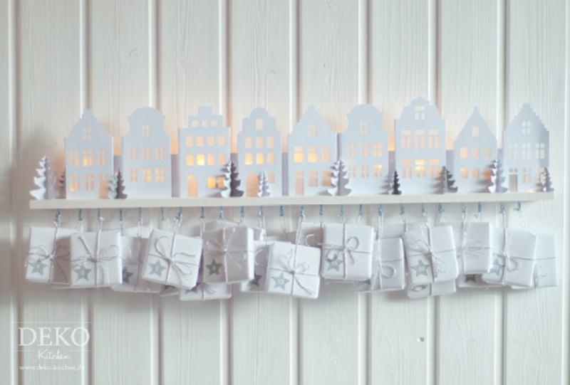 Quanto manca a Natale? Prepara il Calendario dell'Avvento fai da te e inizia il conto alla rovescia sagome casette alberi pini abeti bianchi cartoncino biano luci led pacchetti regalo ganci tavola legno bianco