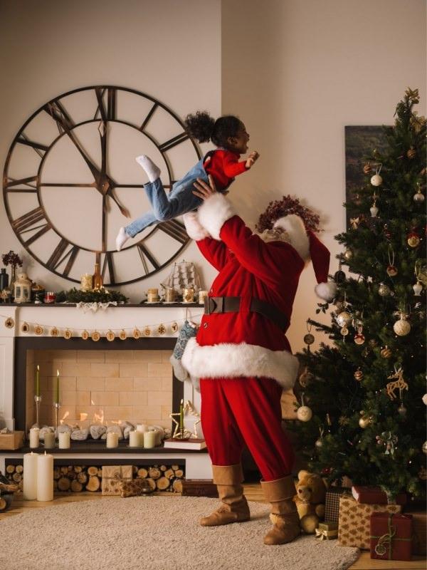 Babbo Natale gioca con bambina facendola vorare in aria davanti Albero
