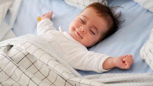 bambino neonato dorme sereno sorriso