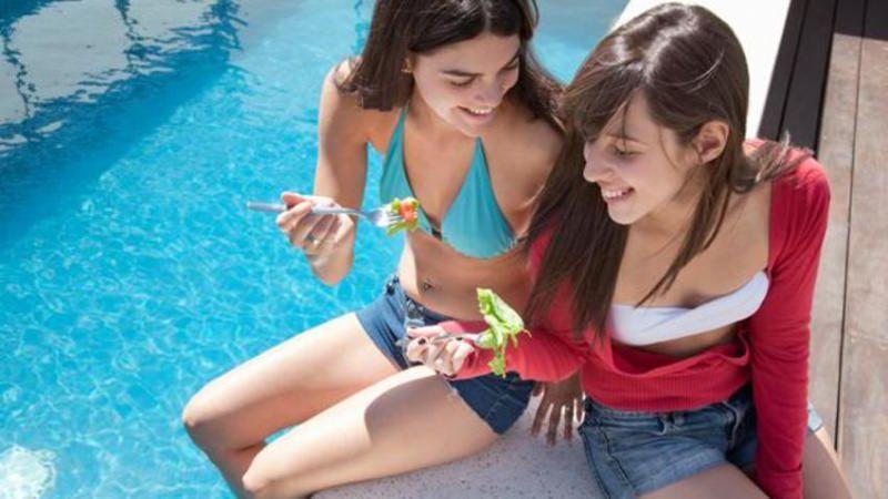 Tutti al mare! Fare il bagno dopo aver mangiato, è una buona idea? estate acqua piscina ragazze mangiano insalata pomodoro forchetta donne bikini turchese shorts jeans donna capelli lunghi castani sorrisi fascia bianca giacca rossa