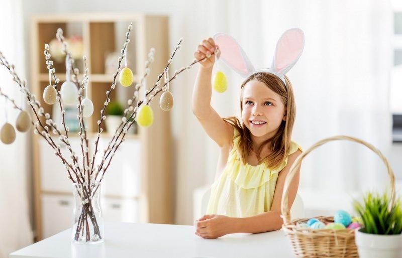 decorazioni rami salice con uova colorate bambina sorriso pasqua