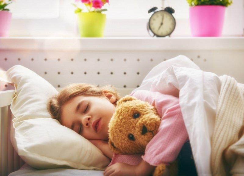 bambina dorme nel letto con il suo peluche orsetto