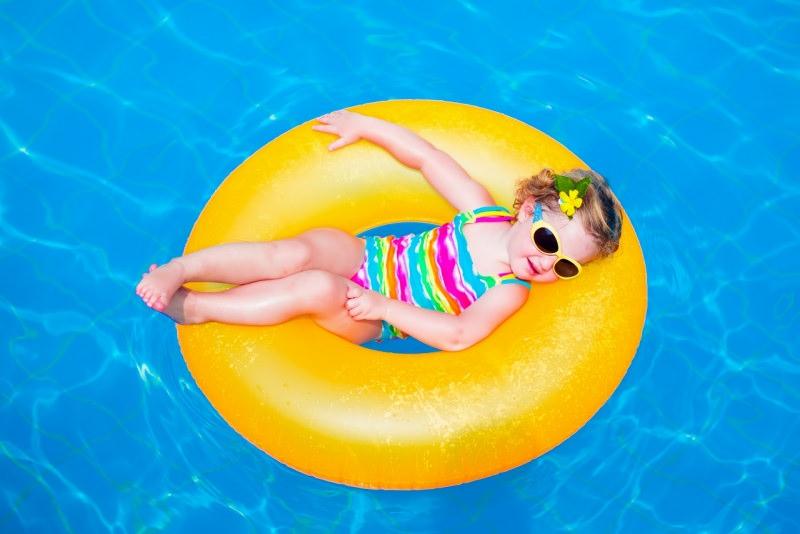 bambina in piscina galleggia ciamnella costume da bagno occhiale da sole protezione solare