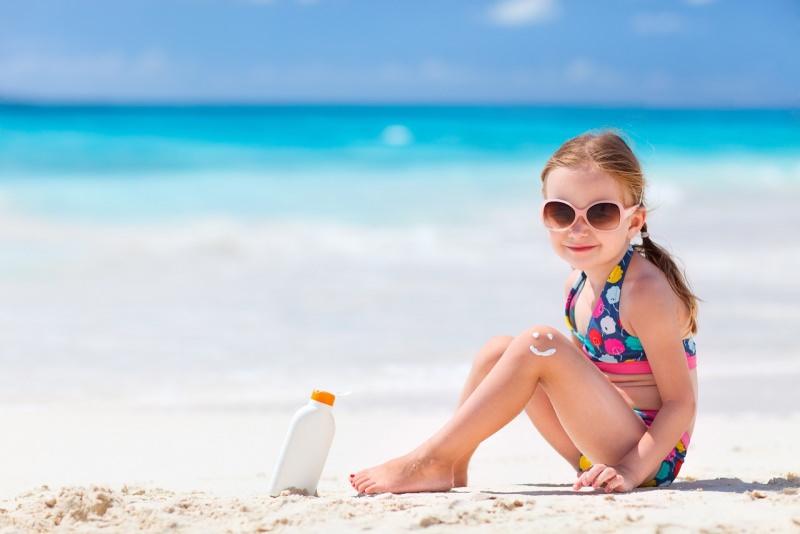 bambina protezione solare sorriso sabbia spiaggia estate mare occhiali da sole