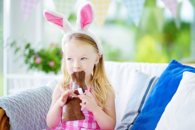 bambina mangia coniglietto cioccolato pasqua orecchie