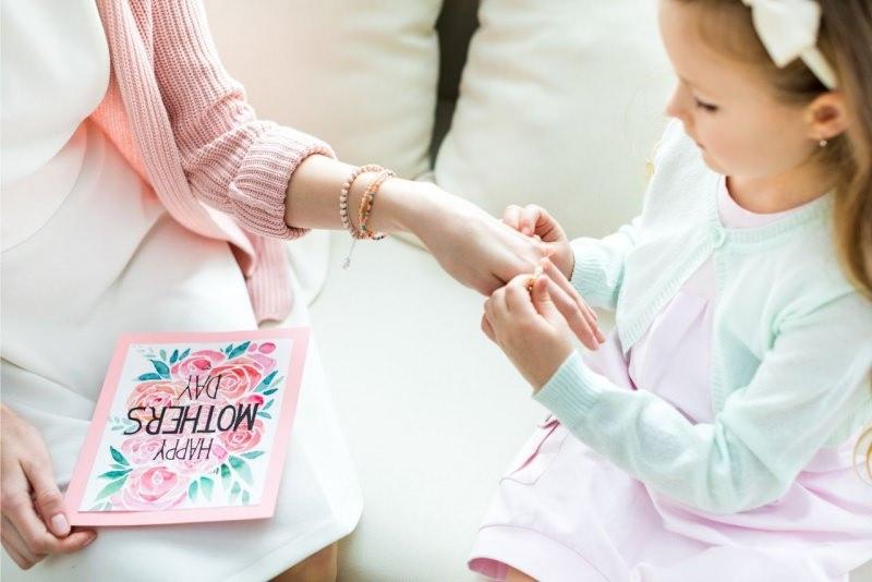 bambina figlia mette bracciale regalo festa della mamma