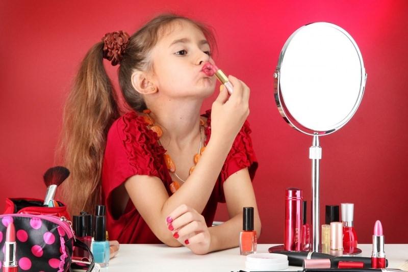 bambina si trucca allo specchio makeu rossetto