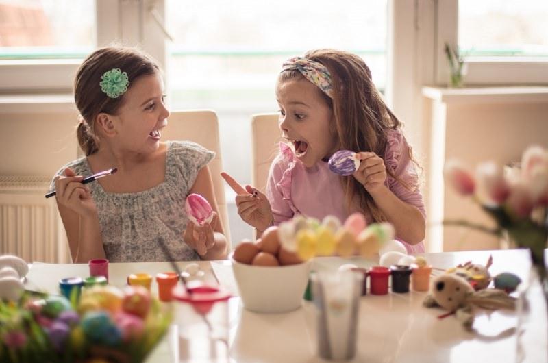 bambine si divertono a dipingere le uova di pasqua colori