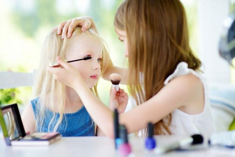 bambina mette mascara makeup alla sua amichetta gioco