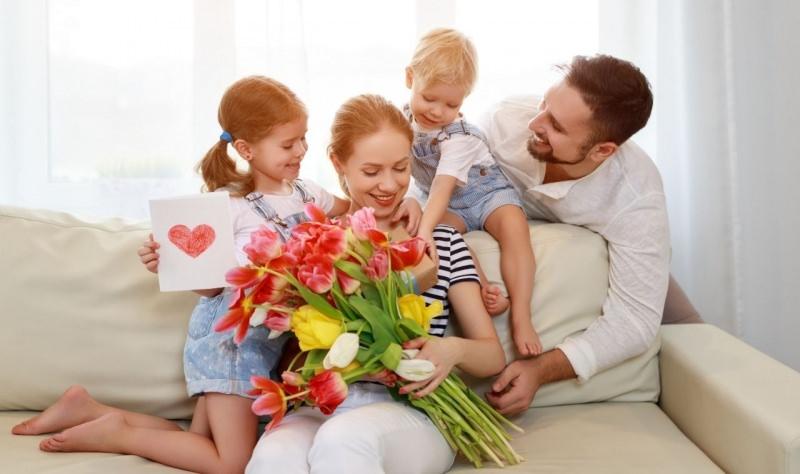 famiglia felice bambini figli e papà danno regalo mamma festa fiori