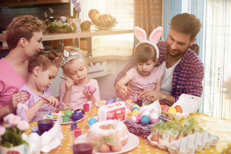famiglia mamma papà bambini bambine dipingono le uova colorate pennelli