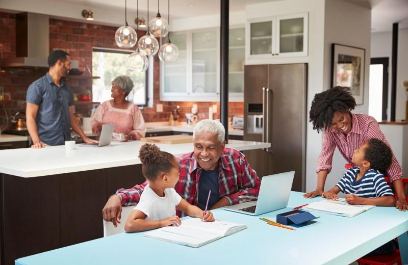 famiglia sta insieme a casa in cucina con notebook e bambini fanno i compiti