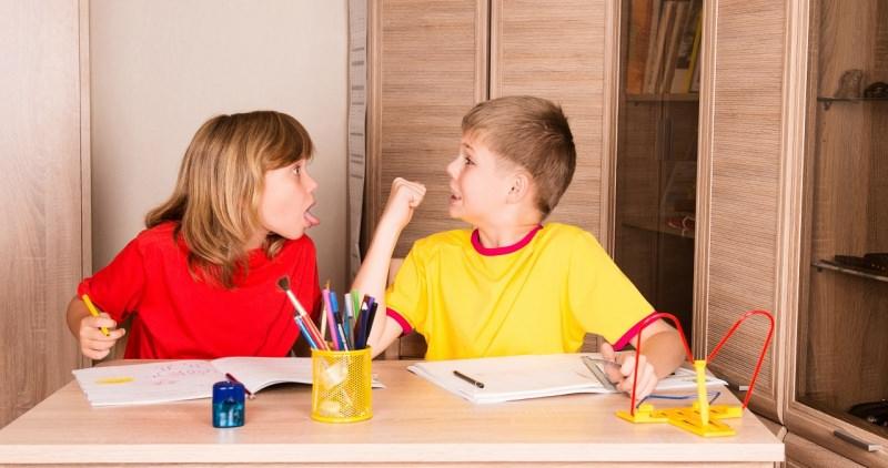 fratelli litigano sorella fa i dispetti a fratello mentre fanno i compiti in casa