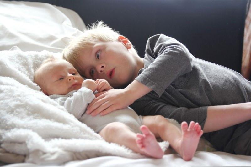 bambino capelli biondi abbraccia fratellino neonato letto