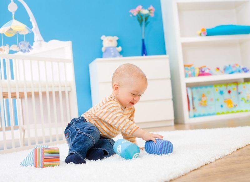 bambino gioca sul tappeto della sua cameretta