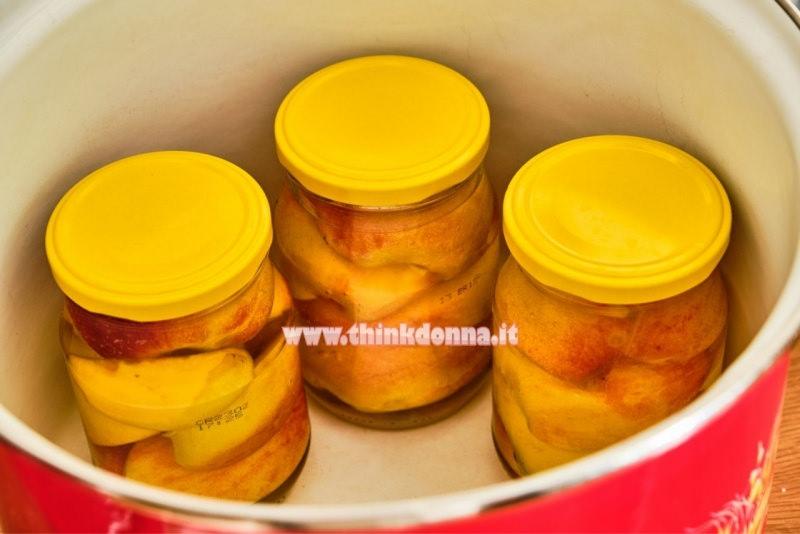 barattoli pesche sciroppate dentro pentola tappo giallo ermetico