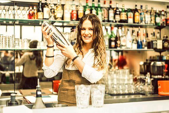 Barman: la professione femminile del presente bartender barlady donna capelli lunghi castani sorriso camicia bianca grembiule dietro al bancone bar bottiglie liquori cocktail shaker bicchieri ghiaccio