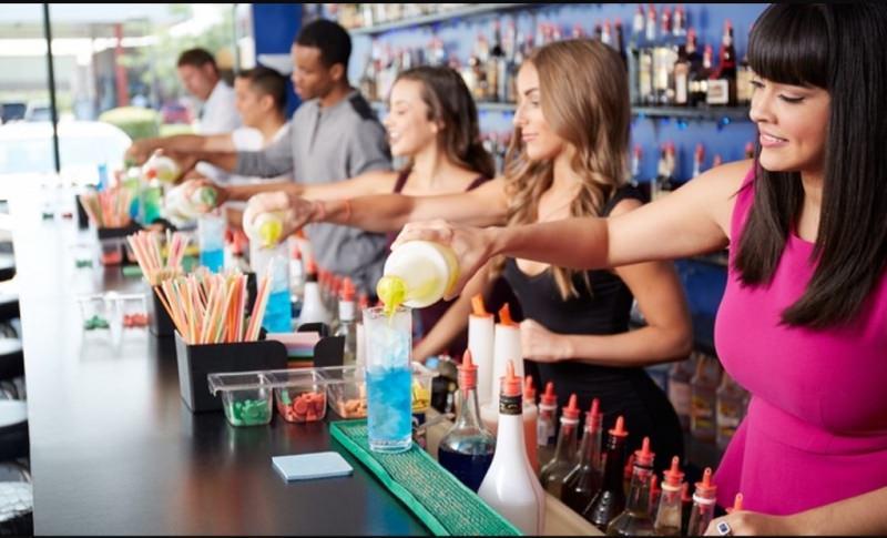 Barman: la professione femminile del presente bartender dietro bancone ragazzi uomini donne barlady cocktail bottiglie corso professionale bicchiere liquido azzurro