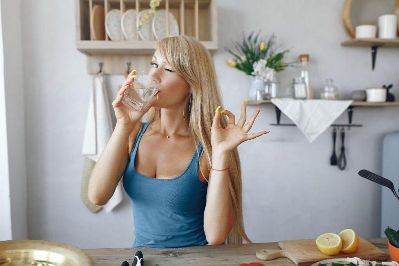 giovane bella donna capelli biondi beve un bicchiere d'acqua in cucina occhiolino ok