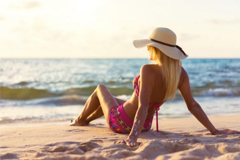 abbronzatura pelle abbronzata donna con cappello di paglia sole sul viso mare sabbia spiaggia