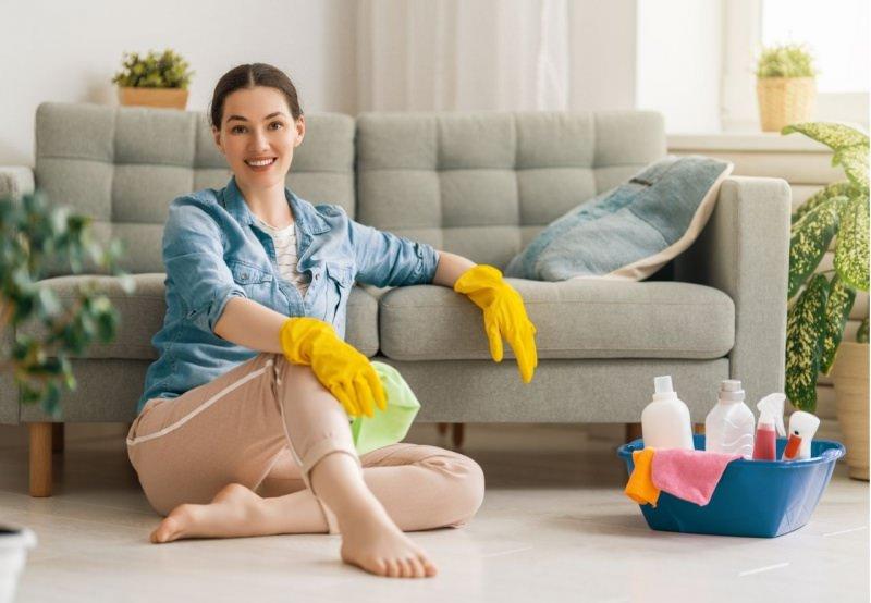 bella donna con sorriso pulizia casa soggiorno divano detersivi