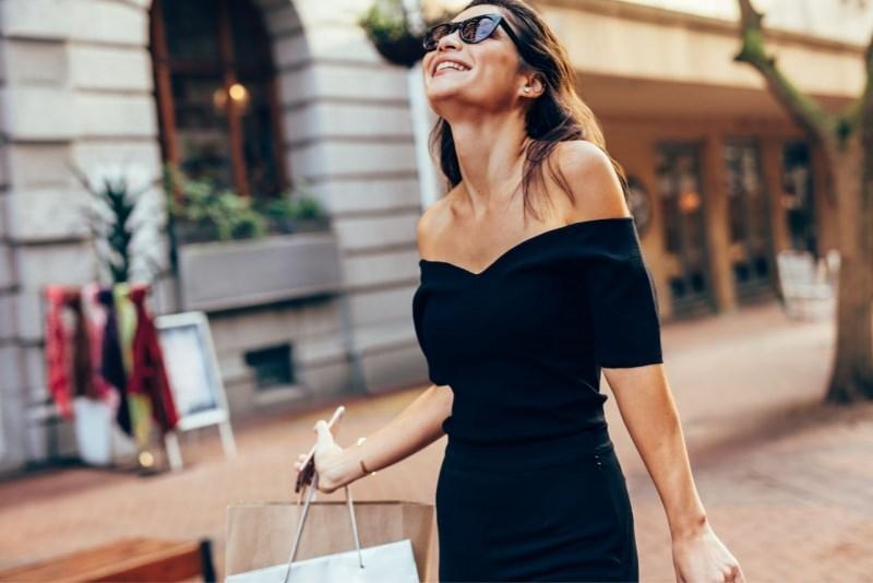donna elegante abito nero con ampia scollatura occhiali da sole shopping