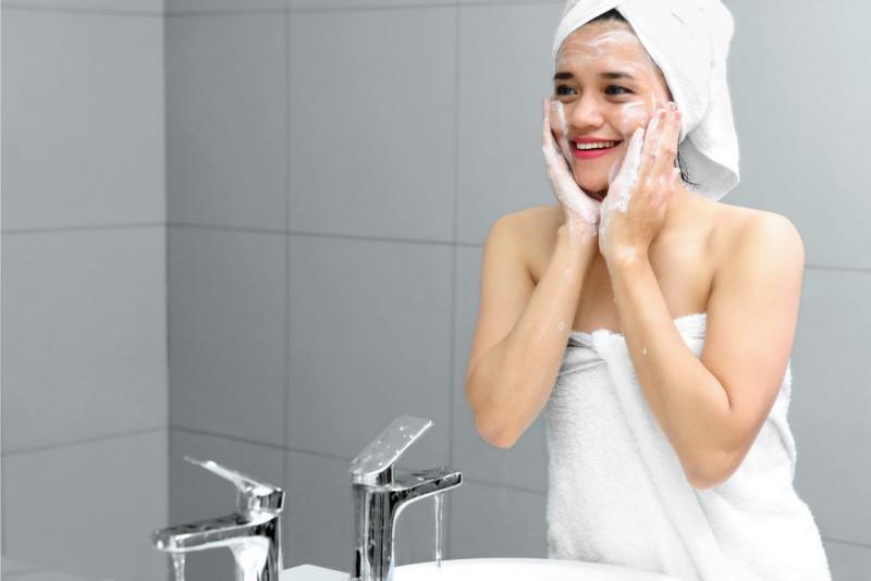 giovane donna con turbante in testa telo spugna pulisce viso con detergente schiumogeno schiuma rubinetto bagno