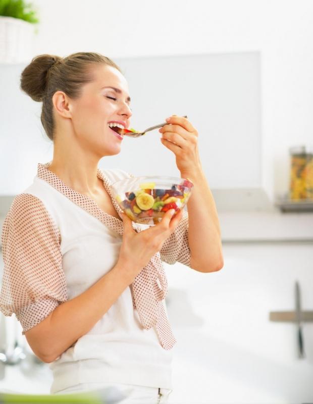 giovane ragazza capelli castani forchetta frutta banana fragole mirtilli mangiare sano
