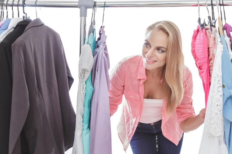 giovane e bella donna capelli lunghi biondi sceglie abiti per ufficio