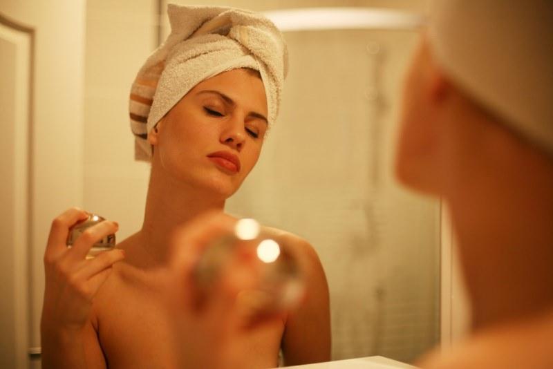 bella donna si mette il profumo allo specchio dopo la doccia turbante telo spugna occhi chiusi