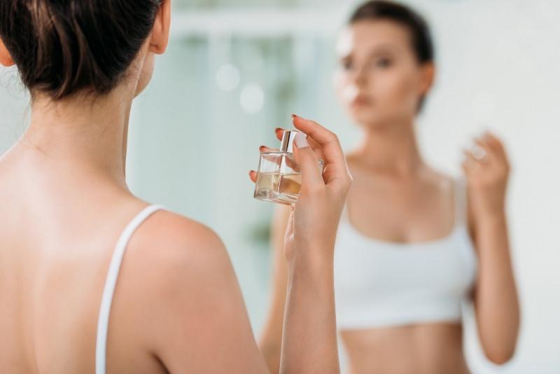 bella donna si spruzza il profumo spray allo specchio bagno